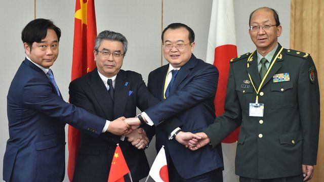 Chinese and Japanese officials shake hands