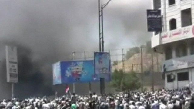 A crowd in Yemen with black smoke rising over the crowd