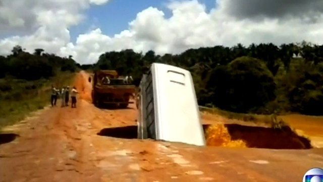 A bus falls into a hole in the road