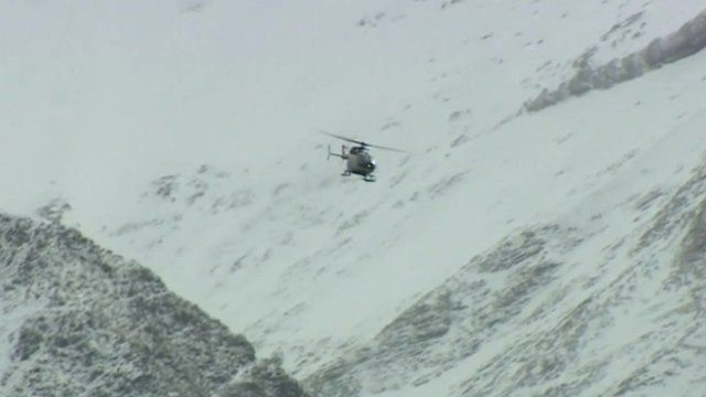 A helicopter flying through a valley