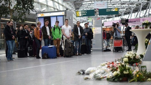 Visitors and travellers stand in a moment of silence at the airport in Duesseldorf, Germany