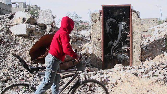 Boy on bike looks at door bearing Banksy artwork