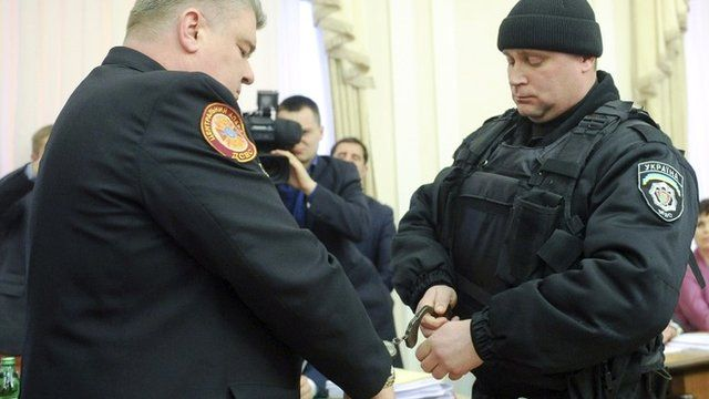 A policeman putting handcuffs on Sergiy Bochkovsky