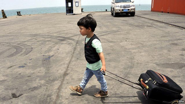 Chinese boy, evacuated from conflict in Yemen, pulling suitcase across port in Djibouti