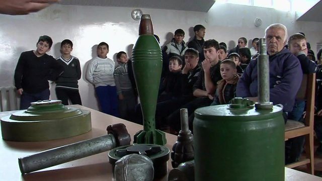 Students in Nagorno-Karabakh looking at ordnance on a table during a lesson on identifying mines and bombs left over from the Armenia-Azerbaijan conflict