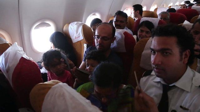 Children sitting on adults laps on board the plane