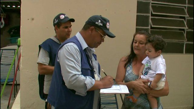 A dengue inspector speaks with a local resident