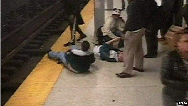 Alfred McNamee lying on ground (r) after being rescued from subway tracks by Charles Collins seen lying on ground (l)