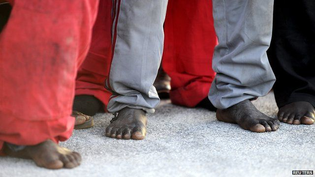 Close up of the bare feet of migrants who have arrived in Sicily