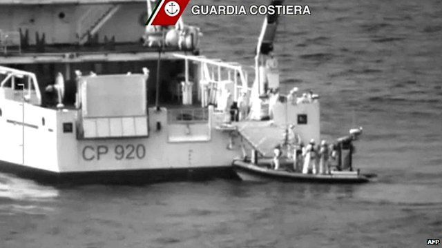 Rescuers take part in an operation off the coast of Sicily