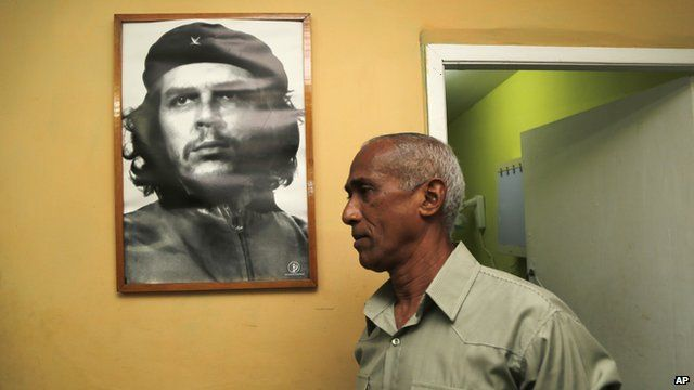 Cuban opposition candidate Hildebrando Chaviano walking beside image of revolutionary leader Che Guevara before casting his vote