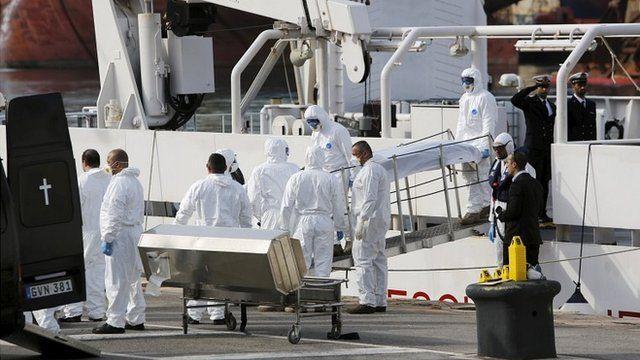 Italian coastguards carry a body from their ship in Malta