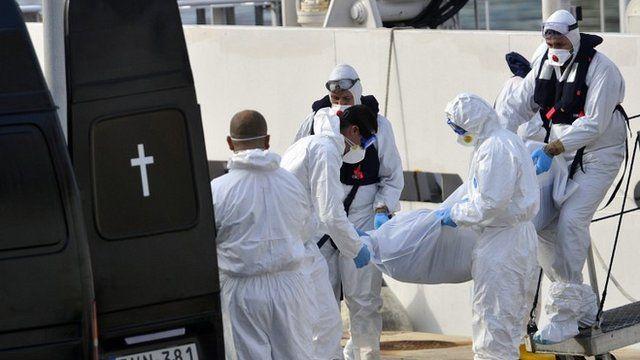 Italian coastguards carry body of migrant from ship at Malta