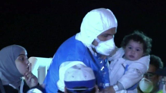 A child and mother are rescued from a migrant boat in Sicily