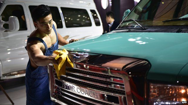 A model cleans a car of Chinese company Star Coach at the 16th Shanghai International Automobile Industry Exhibition in Shanghai
