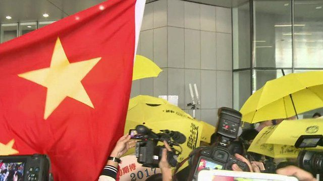 Protestors, some carrying yellow umbrellas, some with a Chinese flag