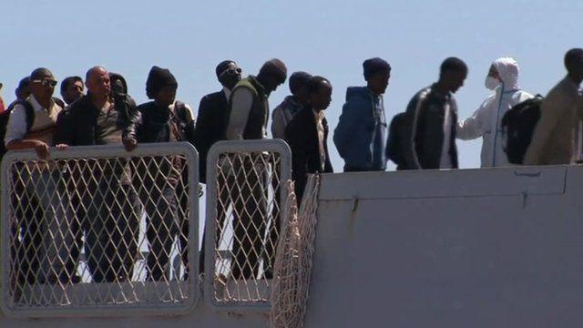 Migrants walking off a boat