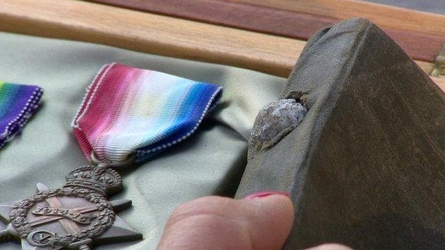 Medal and prayer book with shrapnel in