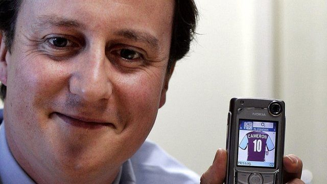 Mr Cameron, pictured in 2005, holding a phone with an image of an Aston Villa shirt with this name on it