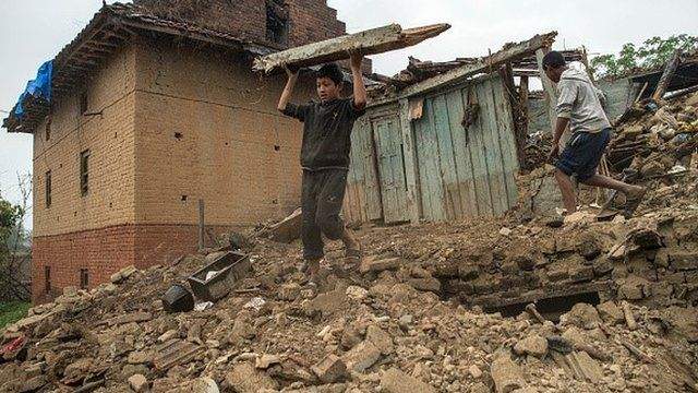 Nepalese boys searching among earthquake rubble