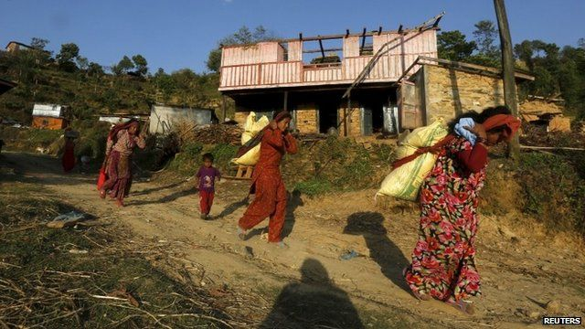 Earthquake victims carry relief materials on their backs at a village in Sindhupalchowk