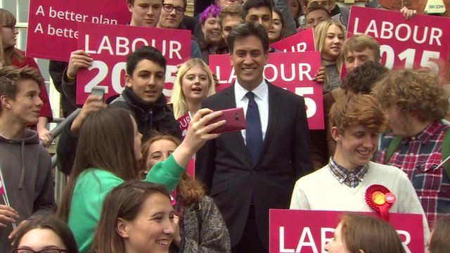 Labour leader Ed Miliband surrounded by young supporters taking selfies as he leaves an event in Brighton