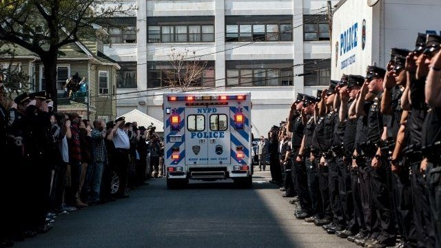 NYPD officers salute as an ambulance carrying the body of officer Brian Moore leaves hospital