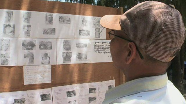Man looks at missing persons board