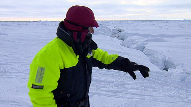 BBC science editor David Shukman stands next to a large crack in the Arctic ice