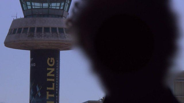 Blurred face of pilot (to avoid identification) in front of an air traffic control tower