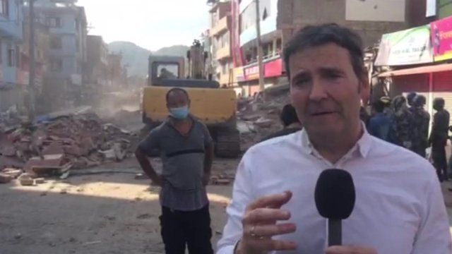 BBC reporter Simon Cox in a Kathmandu street as people in background work to clean up street following Nepal's second earthquake