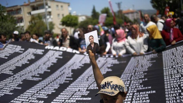 A youth holds a picture of one of the victims of the mining disaster that left over three hundred miners dead, as others hold a banner with their names, during a rally In Soma