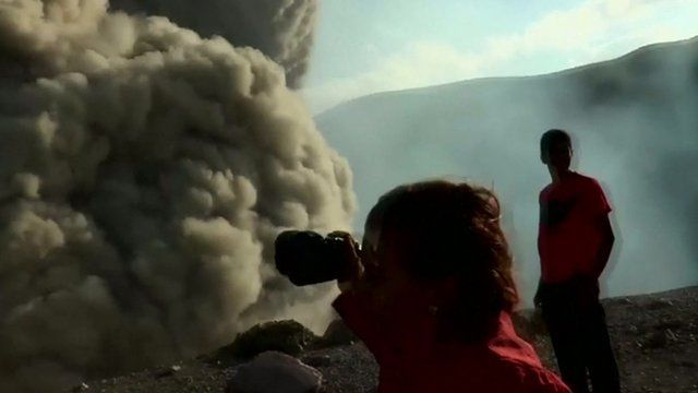 People pointing cameras at cloud of ash