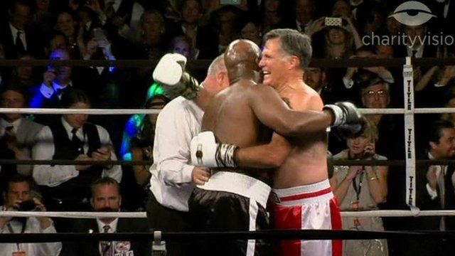 Former Republican presidential candidate Mitt Romney hugs former heavyweight boxing champ Evander Holyfield after the charity fight