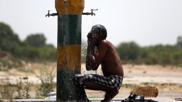 An Indian labourer cools off under a water tap on a hot afternoon in Amritsar, India