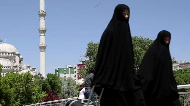 Women walk in front of a mosque