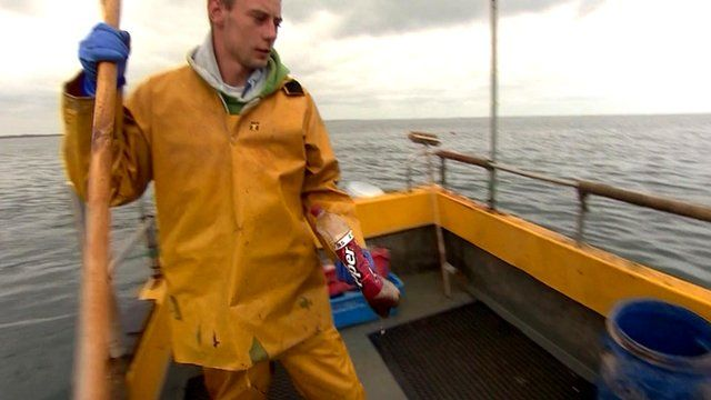 Fisherman picks plastic bottle out of the sea