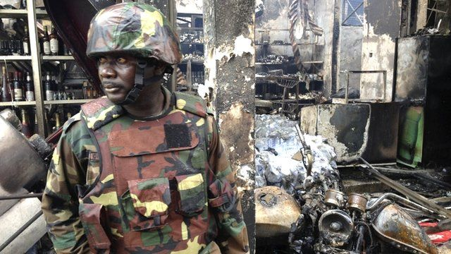 Soldier stands guard at the wreckage of a petrol station in Accra, Ghana