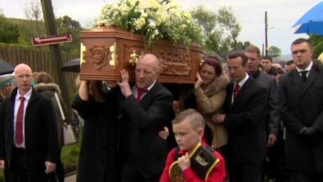 Former world boxing champion Eamonn Magee Sr carries the coffin of his son Eamonn Magee Jr