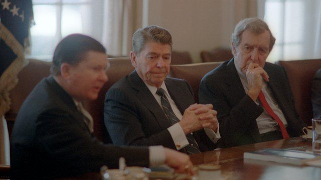 President Ronald Reagan seated at a meeting