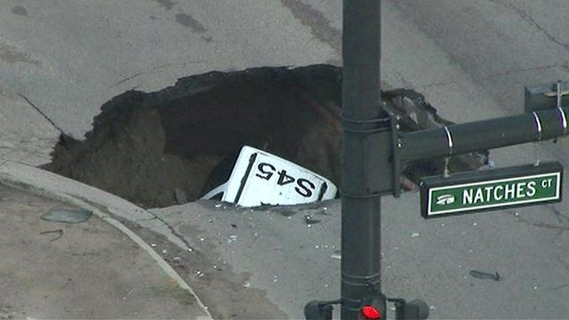 aerial view of car in sinkhole
