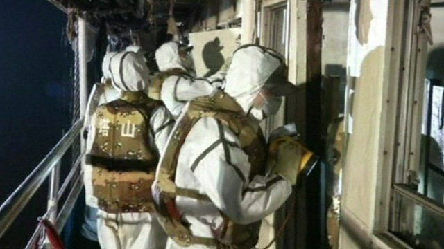 Rescue workers look inside cabins