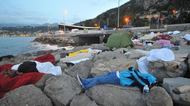 People sleeping on rocks at border between Italy and France