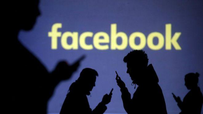 Una imagen que muestra siluetas de usuarios de teléfonos celulares junto a la proyección del logo de Facebook.