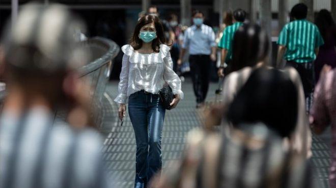 Mulher anda na rua em Hong Kong