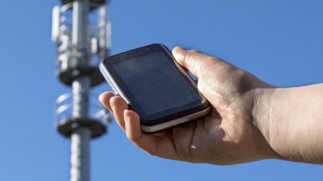 Teléfono móvil frente a una torre de antena de celular.