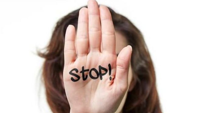 Woman holding up her hand with 'stop' written on her palm