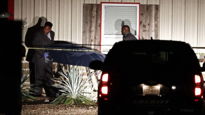 Officials are seen removing a covered stretcher from the party venue