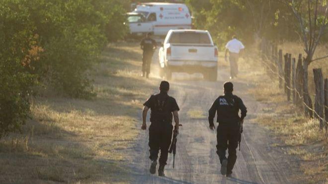 Dos policías corren a la escena del crimen en Colima.