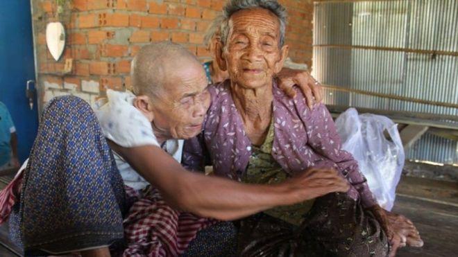 Bun Sen e Bun Chea aparecem sentadas e abraçadas em ambiente interno de casa